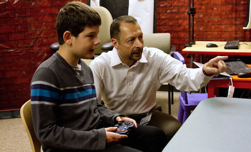 Tony Simon shows a student his video game, Fastbrain